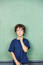 Elementary school student in front thinking of empty chalkboard Royalty Free Stock Photography