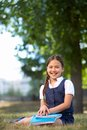 Elementary schoolgirl image of cute with copybooks in summer park Stock Photo