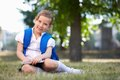 Elementary student image of cute schoolgirl with backpack sitting on grass in summer park Stock Photos