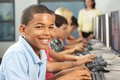 Elementary students working at computers in classroom looking camera smiling Stock Images