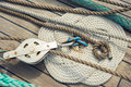 Elements of equipment of a yacht rope braided in celtic knot work shape on wooden sailing ship floor with steel pulley Royalty Free Stock Image