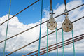 Elements of equipment of a yacht sailboat stainless pulleys and ropes detail on blue sky with white clouds Stock Photography
