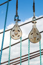 Elements of equipment of a yacht sailboat stainless pulleys and ropes detail on blue sky with white clouds Royalty Free Stock Photography