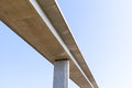 Elevated concrete road bridge from below with plain blue sky an seen supported by a single visible pillar background Royalty Free Stock Photography