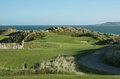 Elevated links par golf hole with large sand dunes and ocean horizon an tee fencing on top in background tee box in foreground Royalty Free Stock Image