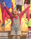 Eleven-year old girl singing on stage in school play Royalty Free Stock Photo