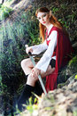 Elf girl on the rock in red cloak posing outdoor Royalty Free Stock Photo