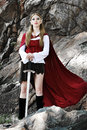 Elf girl on the rock in red cloak posing outdoor Stock Photo