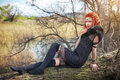 Elf woman with fiery hair on a log. Royalty Free Stock Photo