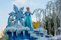 Elsa of frozen fame on float in disneyland parade from the popular computer animated musical fantasy comedy is waving atop a Stock Photo