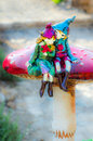 Elves in love two a romantic happy couple of sit on top of a magic mushroom she is holding a bouquet and he is holding her Stock Image