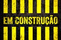 Em Construcao In Portuguese: Under construction warning sign with yellow and black stripes painted over concrete wall background Royalty Free Stock Photo