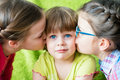 Embarrassed little girl kissed by two sisters. Royalty Free Stock Photo