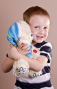 Embrace boy s with bear in the studio Royalty Free Stock Photos