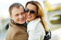 In embrace portrait of happy urban couple looking at camera outdoors Stock Photo