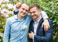 Embracing groom and friend at park portrait of Stock Image