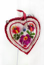 Embroidered pincushion in form heart with needles Royalty Free Stock Photo