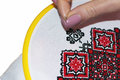 Embroidering a cross on a white fabric with red and