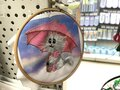 Embroidery `Cat under an umbrella` in a embroidery frame