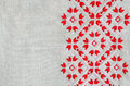Embroidery design by red and white cotton threads on flax. Christmas background with embroidery. Royalty Free Stock Photo