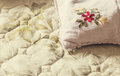 Embroidery details of a pillow on bed sheet closeup of work Royalty Free Stock Photo