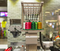Embroidery machine with various color thread inside sport fashion shop Royalty Free Stock Photo