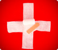 Emergency cross symbol of made from bandage that illustrates concept of first aid Royalty Free Stock Images