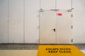 Emergency exit door with keep clear warning message on floor copy space on wall Royalty Free Stock Photo
