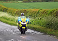 Emergency police motor cycle with blue lights flashing a cyclist on a country road in the united kingdom Stock Photography