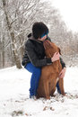 Emo boy is cuddling his dog funky having fun with in the snow Royalty Free Stock Photo
