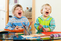 Emotional children playing with paper and pencils Royalty Free Stock Photo