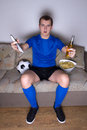 Emotional football supporter watching tv with beer and chips Royalty Free Stock Images
