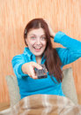 Emotional girl changing channels with clicker Royalty Free Stock Photography