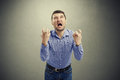 Emotional man looking up and screaming over dark background Royalty Free Stock Images