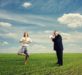 Emotional man screaming at calm woman men women in the field Stock Photography