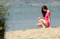 Emotional picture of a cute lady by a lake wearing jean shorts and shirt sitting on legs in profile view looking down horizontal Royalty Free Stock Photos