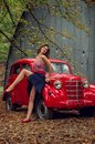 stock image of  Emotional portrait. Pin-up girl posing near by a red russian retro car.The model laughs loudly, flirtatiously showing slender legs