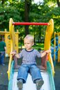 Emotions in the child`s view, confusion and sadness in the eyes of the little boy sitting on the children`s hill Royalty Free Stock Photo