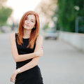 Emotive cute young redhead woman in a black dress with slight smile Stock Photography