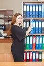Empleado de mujer en la oficina que se coloca al lado del gabinete con los archivos documentales Fotografía de archivo libre de regalías