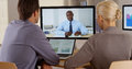 Employees listening to manager in a video conference medium shot of two business colleagues holding Royalty Free Stock Images