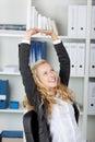 Empresaria with arms raised que se sienta en oficina Imagenes de archivo