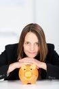 Empresaria seria with piggy bank en el escritorio Foto de archivo libre de regalías