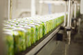 Empty aluminum cans for drinks move on conveyor at large factory shallow depth of field Royalty Free Stock Photo