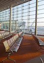 Empty armchairs in hall of expectation of airport and plane behind window Royalty Free Stock Photo