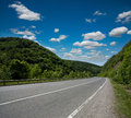 Empty asphalt road highway in the forested mountains, on sky Royalty Free Stock Photo
