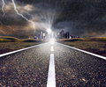 Empty asphalt road towards a city in storm Royalty Free Stock Images