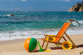Empty beach chair with flowers and toys at the sea Royalty Free Stock Photos