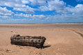 Empty beach driftwood blue sky with log vehicle tracks in sand to ocean white fluff clouds Royalty Free Stock Photography