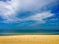 Empty beach with golden sand blue waters and sky Royalty Free Stock Photo